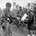 Brian Wilson checks a Vietnamese civilian's identification card, 1967